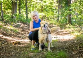 07/21/2020 - Groton, Mass. - Brooklyn and Jayne Smith pose for a photo, along one of their usual walking paths on July 21, 2020. Brooklyn, a golden retriever, contracted tetanus on a walk and was successfully treated at the Foster Hospital for Small Animals at Cummings School of Veterinary Medicine. (Alonso Nichols/Tufts University)