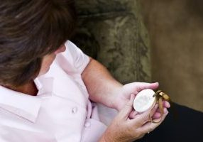 a middle aged woman remembering and mourning for a deceased pet dog. She is holding a plaster cast of his paw print.